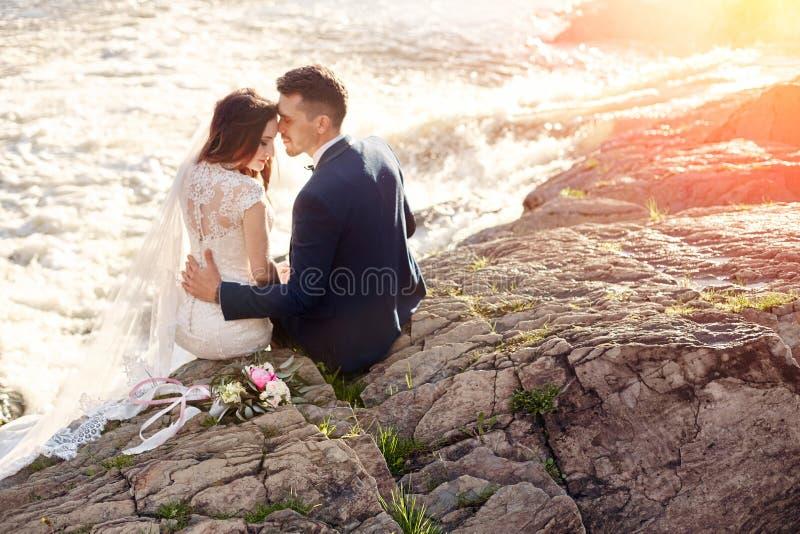 Mooie paarliefde die terwijl het zitten op rotsen dichtbij rivier kussen stock afbeelding