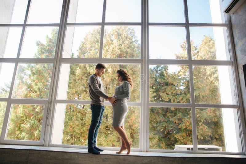 Mooie paartribune voor groot venster in studio Zwangere vrouw met haar echtgenoot stock foto's