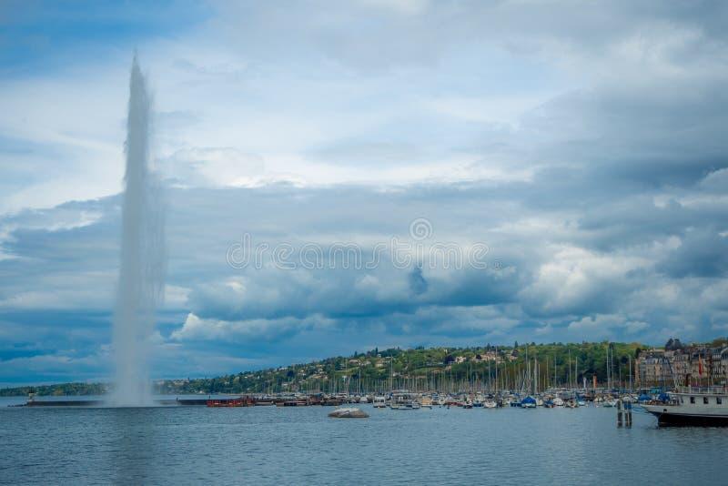 Mooie panoramamening van het meer van Genève en de fontein van Straald 'eau met boten op bewolkte hemel en bergenachtergrond royalty-vrije stock foto