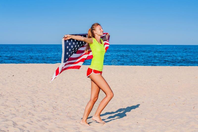 Mooie patriottische vrolijke vrouw die een Amerikaanse vlag op het strand houden stock afbeeldingen