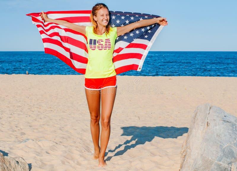 Mooie patriottische vrolijke vrouw die een Amerikaanse vlag op het strand houden royalty-vrije stock afbeelding