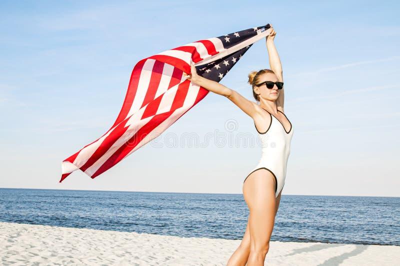 Mooie patriottische vrouw die een Amerikaanse vlag op het strand houden De Onafhankelijkheidsdag van de V.S., 4 Juli royalty-vrije stock foto's