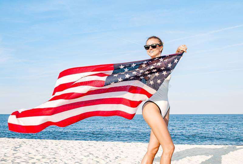 Mooie patriottische vrouw die een Amerikaanse vlag op het strand houden De Onafhankelijkheidsdag van de V.S., 4 Juli stock afbeelding