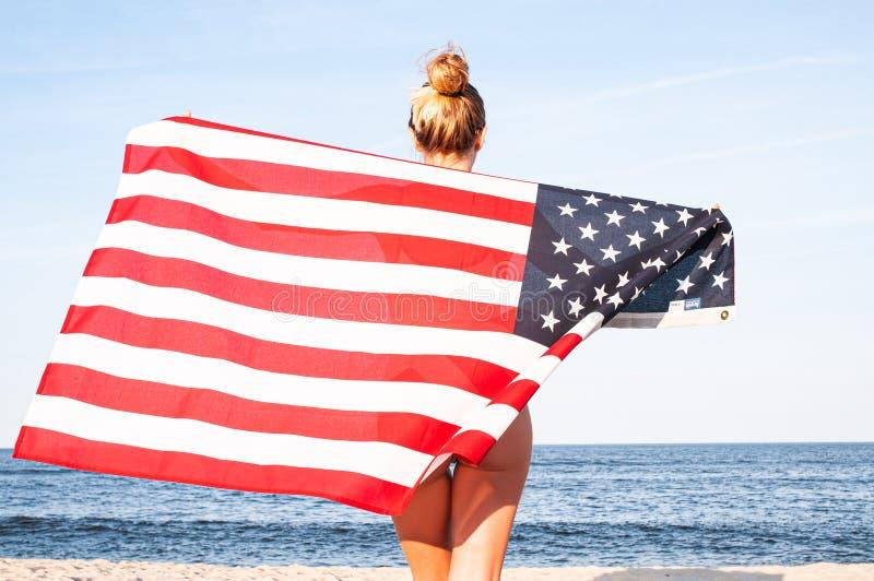 Mooie patriottische vrouw die een Amerikaanse vlag op het strand houden De Onafhankelijkheidsdag van de V.S., 4 Juli Het concept  royalty-vrije stock foto's