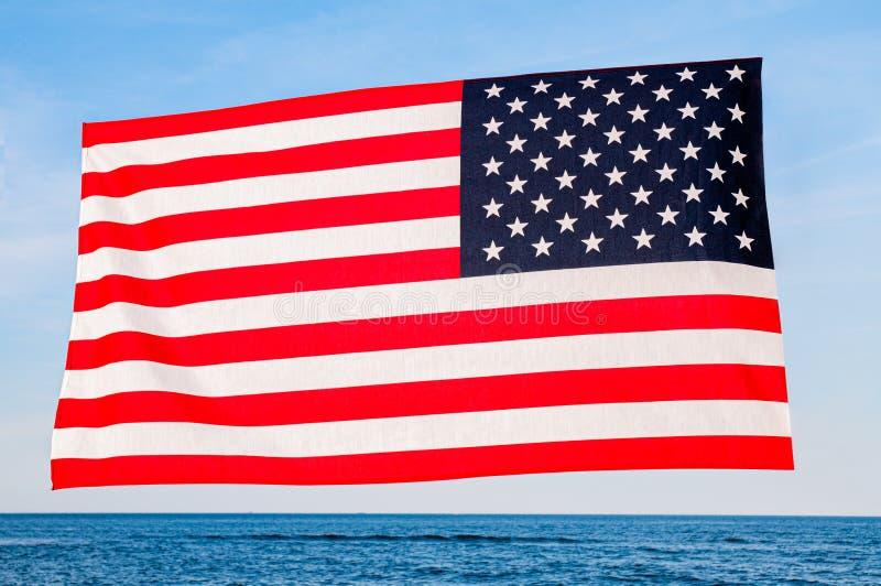 Mooie patriottische vrouw met Amerikaanse vlag op het strand De Onafhankelijkheidsdag van de V.S., 4 Juli Het concept van de vrij royalty-vrije stock afbeeldingen