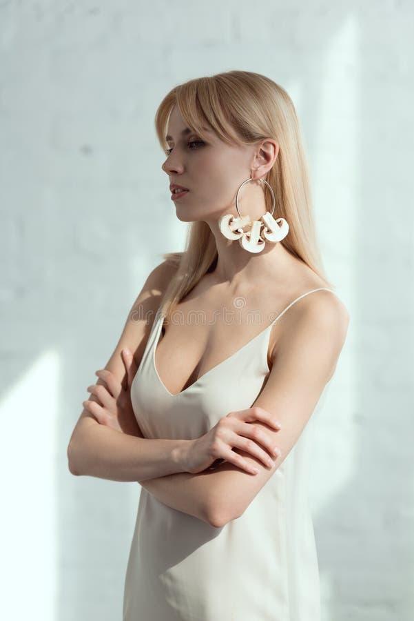 mooie peinzende die vrouw in kleding met oorring van paddestoelenveganist wordt gemaakt royalty-vrije stock fotografie