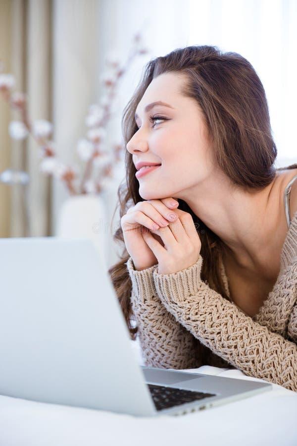 Mooie peinzende jonge vrouw die laptop bij bed en het dromen met behulp van royalty-vrije stock afbeelding