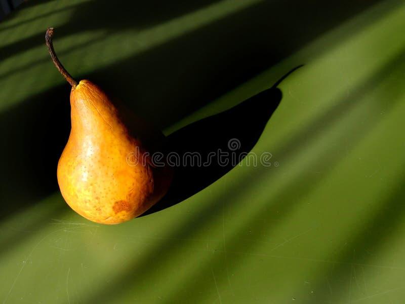 Mooie perenclose-up in het zonlicht met schaduw op een groene lijstachtergrond - artistiek fruitconcept stock foto