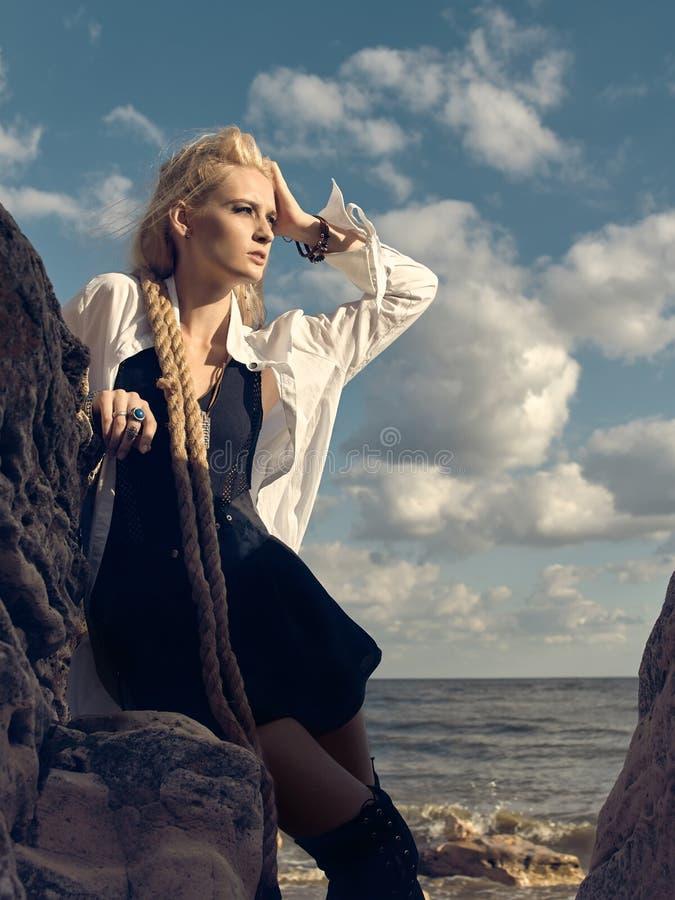 Mooie piraatvrouw die zich op het strand in laarzen bevinden royalty-vrije stock fotografie