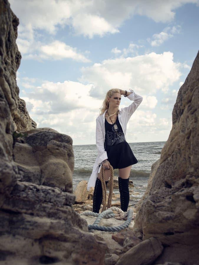 Mooie piraatvrouw die zich op het strand in laarzen bevinden stock foto