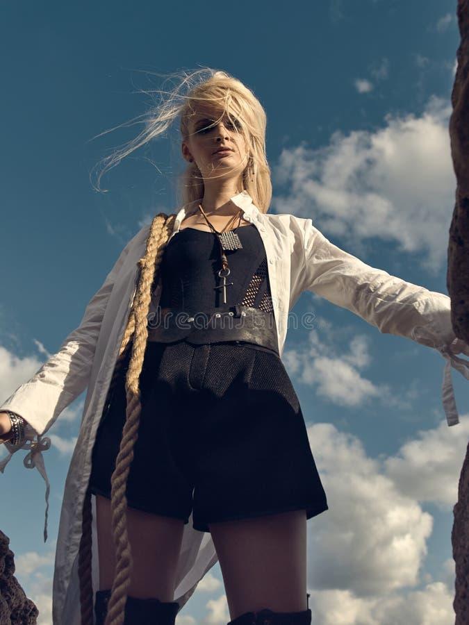 Mooie piraatvrouw die zich op het strand in laarzen bevinden royalty-vrije stock foto's