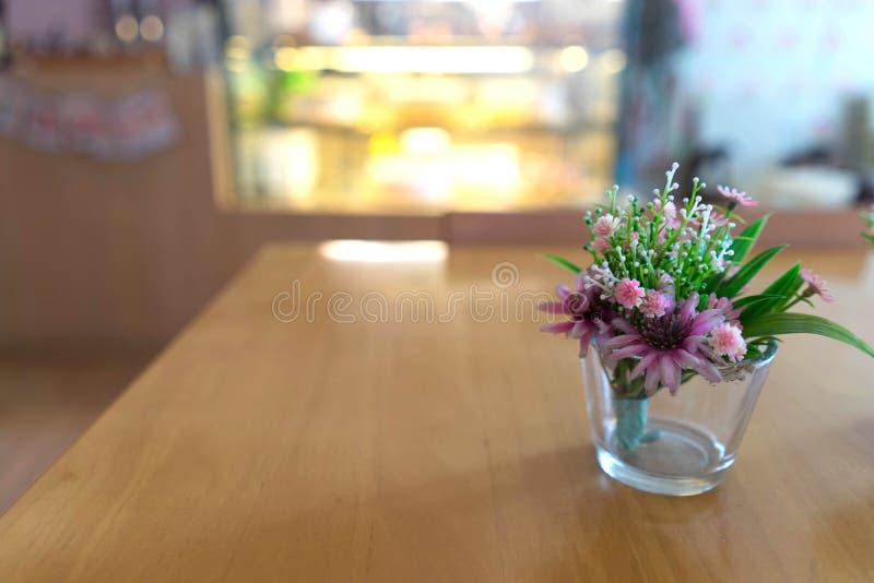 Mooie plastic bloemen op glasvaas op houten lijst in bakker royalty-vrije stock afbeeldingen