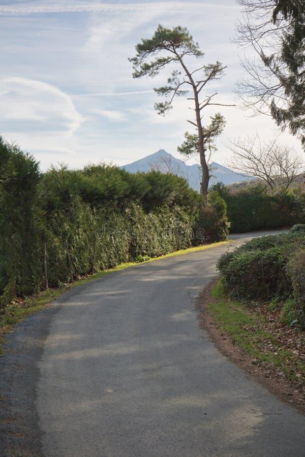 Mooie plattelandsweg met bergla die rhune in Baskisch land stijgen stock afbeeldingen
