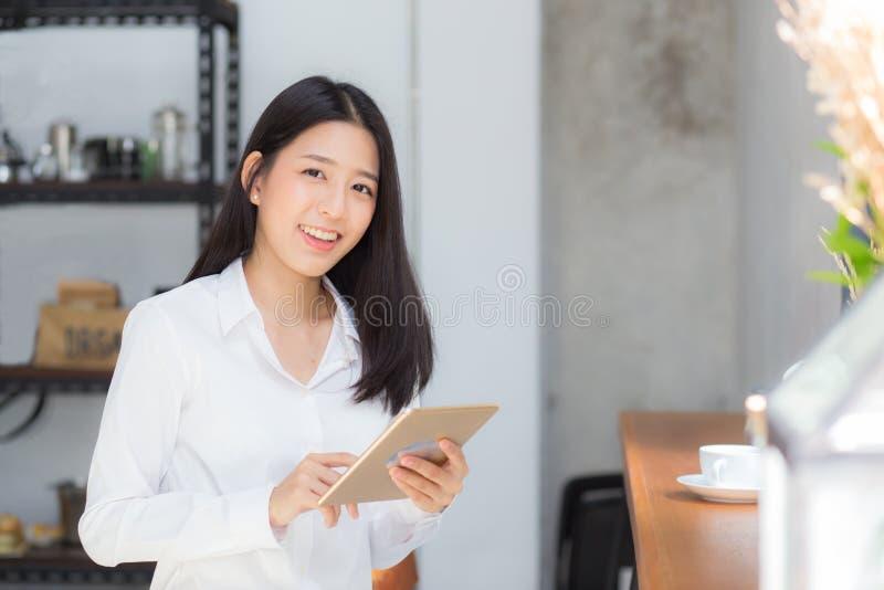 Mooie portret jonge Aziatische vrouw die tabletcomputer in de koffiewinkel met behulp van stock afbeelding