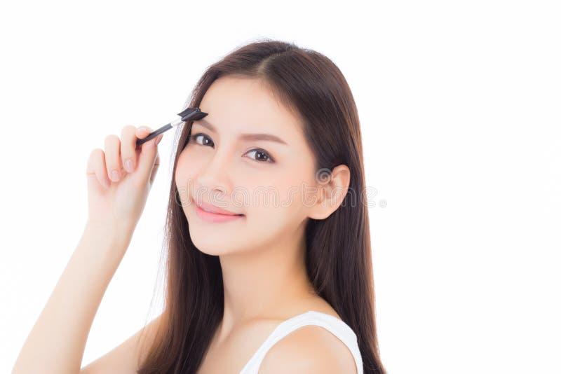 Mooie portret jonge Aziatische vrouw die wenkbrauw of wimper met make-upborstel toepassen die op witte achtergrond wordt geïsolee stock foto