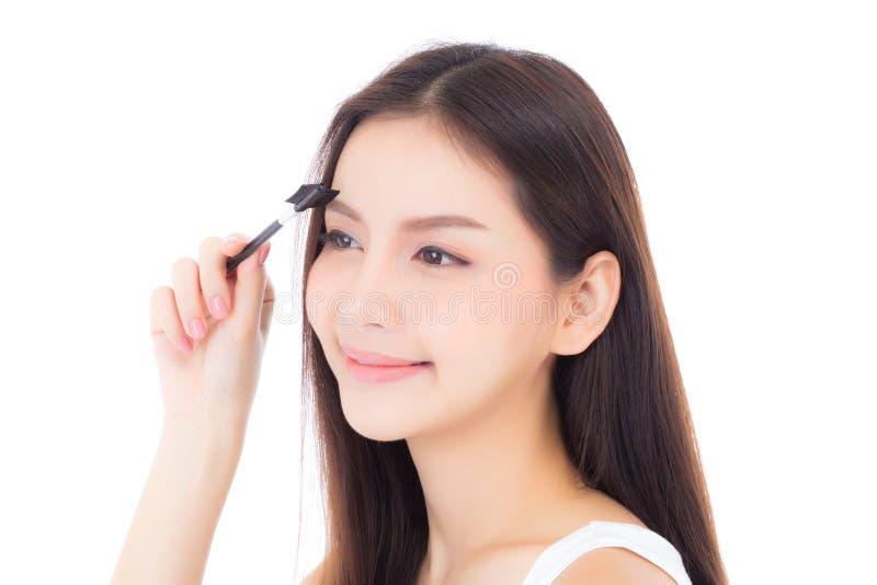 Mooie portret jonge Aziatische vrouw die wenkbrauw of wimper met make-upborstel toepassen die op witte achtergrond wordt ge?solee stock afbeeldingen