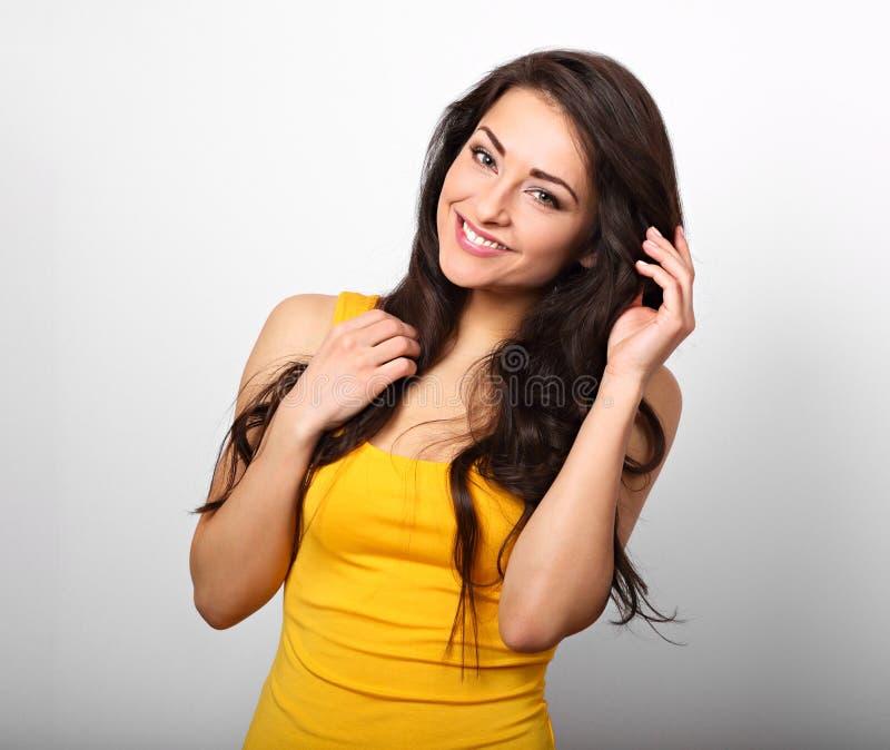 Mooie positieve gelukkige vrouw in geel overhemd en lang haar ook stock fotografie