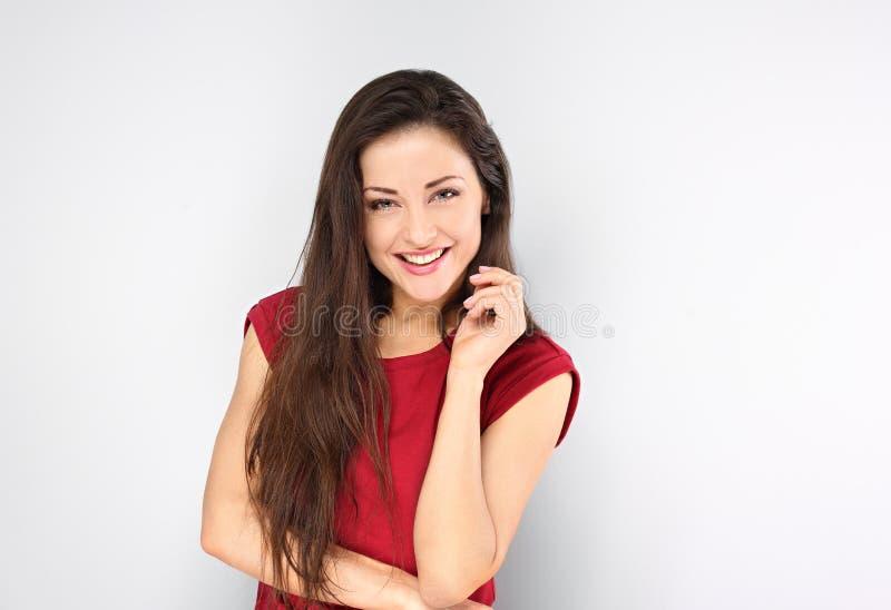 Mooie positieve jonge gelukkige vrouw met hand onder het gezicht die en in toevallig rood overhemd en lang haar op blauw denken k royalty-vrije stock foto's