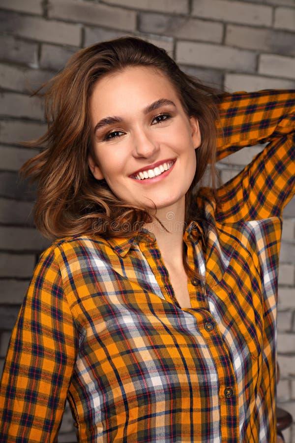 Mooie positieve toothy glimlachende vrouw die gelukkig in toevallig oranje celoverhemd op achtergrond van de baksteen de blauwe s stock afbeelding