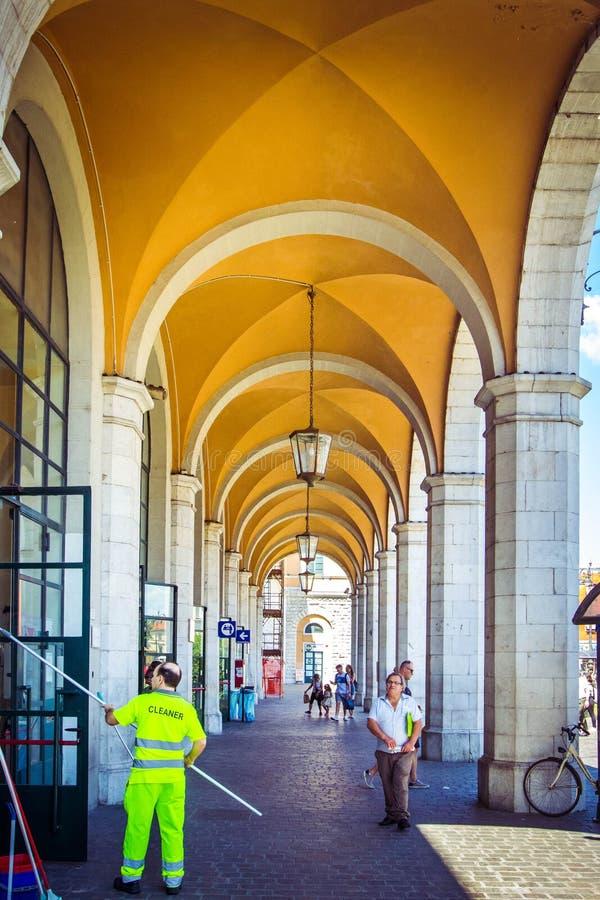 Mooie post in Pisa met witte pijlers en gele bogen, met werkende reinigingsmachines en toeristen, Pisa, Italië royalty-vrije stock fotografie