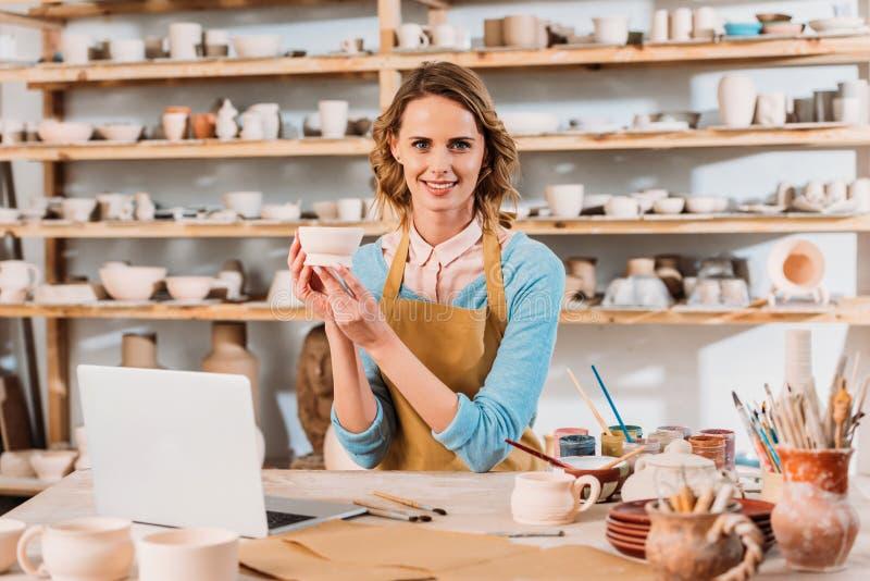 mooie pottenbakker met keramiek en laptop royalty-vrije stock afbeelding