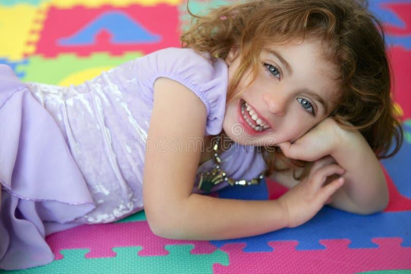 Mooie prinsesmeisje het glimlachen het liggen vloer stock foto