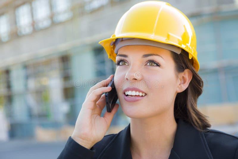 Mooie Professionele Jonge Vrouwencontractant die Bouwvakker op Plaats dragen die Telefoon met behulp van stock foto