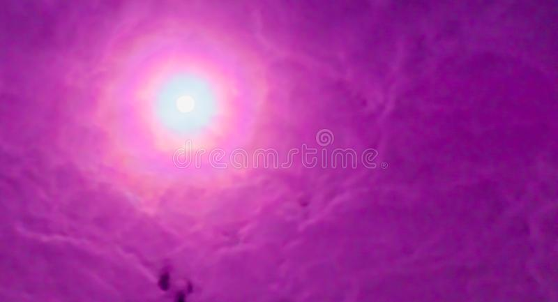 Mooie purpere bewolkte hemel met een heldere zon die door de wolken, de hoopvolle en inspirerende achtergrond glanzen stock foto