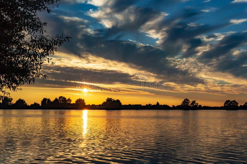 Mooie purpere bewolkte hemel tijdens zonsondergang in plas van meerzoetermeerse royalty-vrije stock afbeelding