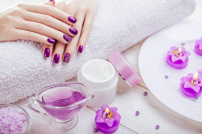 Mooie purpere manicure met kuuroordhoofdzaak stock afbeelding