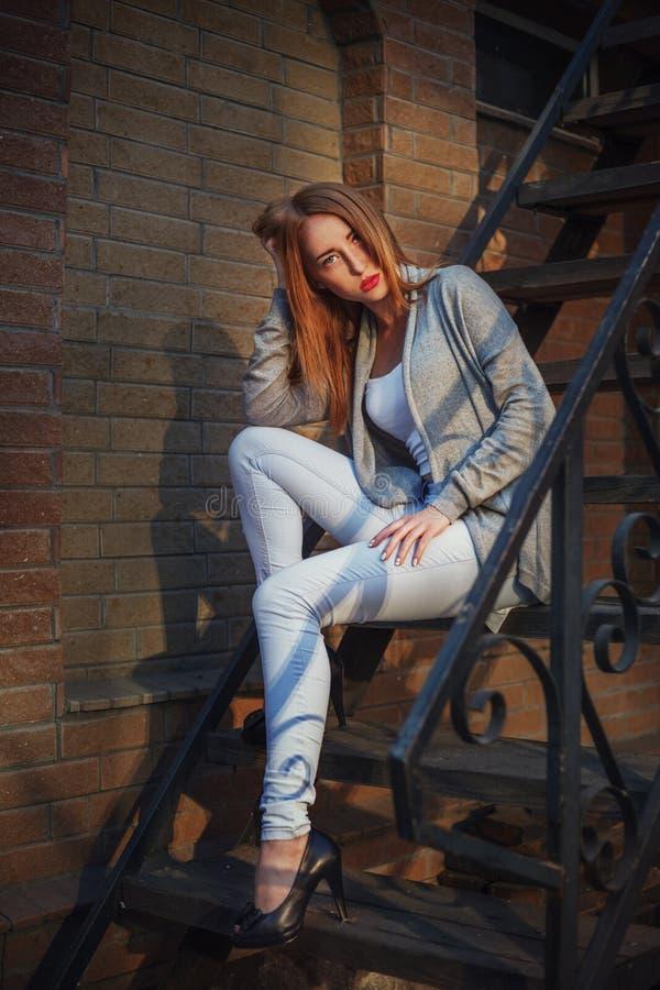 Mooie redhair jonge vrouw in het aardige sluiten, hoge hielenschoenen Het zitten op treden De foto van de manier royalty-vrije stock fotografie