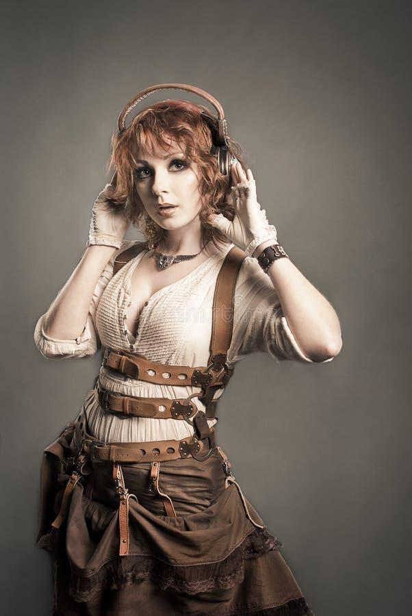 Mooie redhairvrouw die aan muziek met hoofdtelefoons luisteren Oud royalty-vrije stock afbeelding