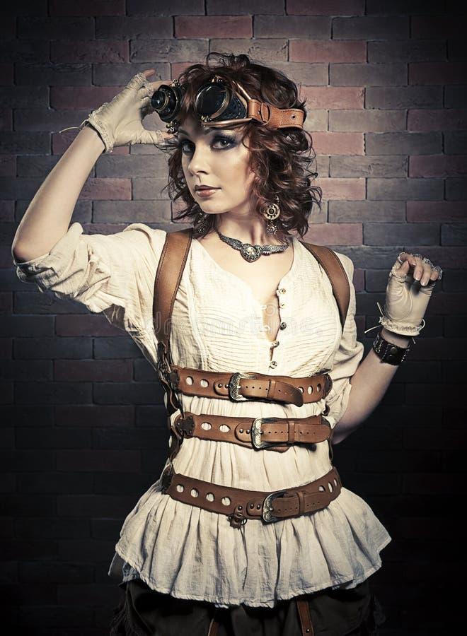 Mooie redhairvrouw met steampunkbeschermende brillen stock afbeeldingen