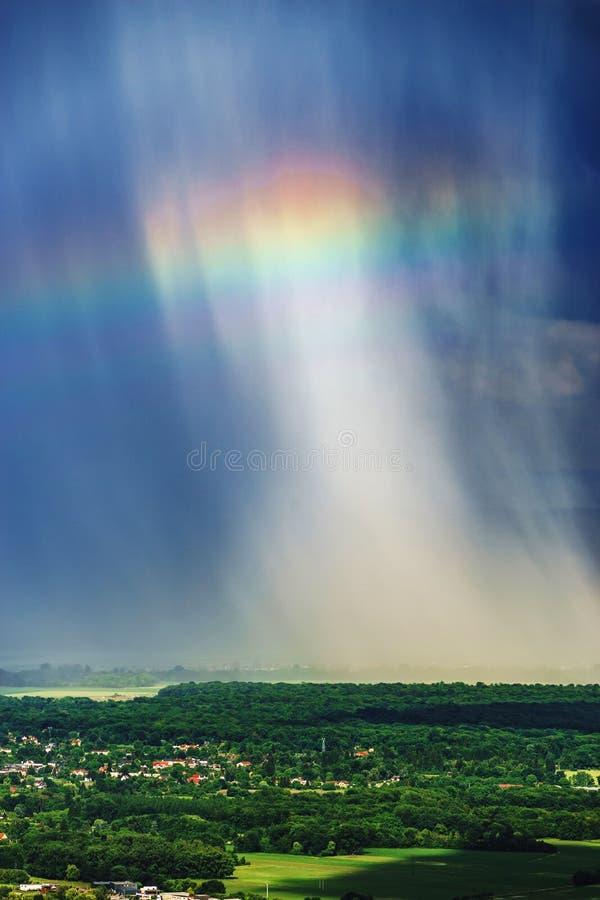 Mooie regenboog met regenachtige wolken, kleurrijke de zomermening stock afbeelding
