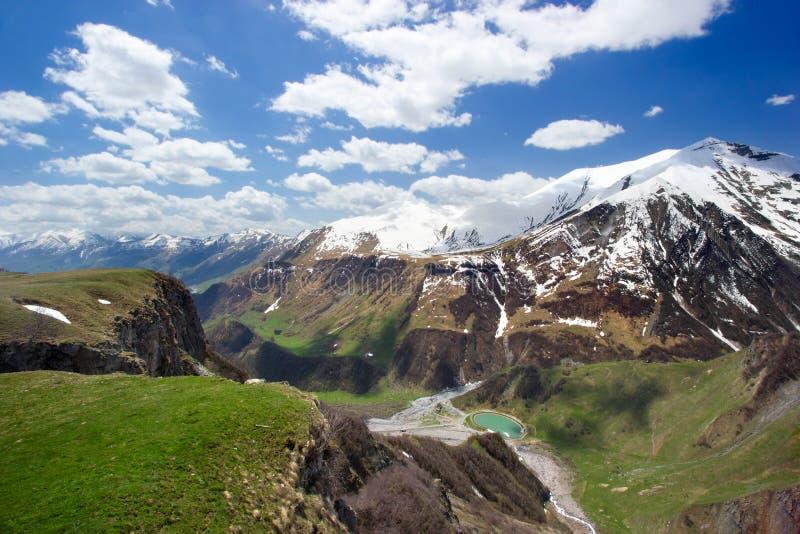 Mooie reusachtige bergenpieken in sneeuw, blauwe hemel, witte wolken, blauw meer bij de voet van de berg, groene heuvels, groene  royalty-vrije stock foto