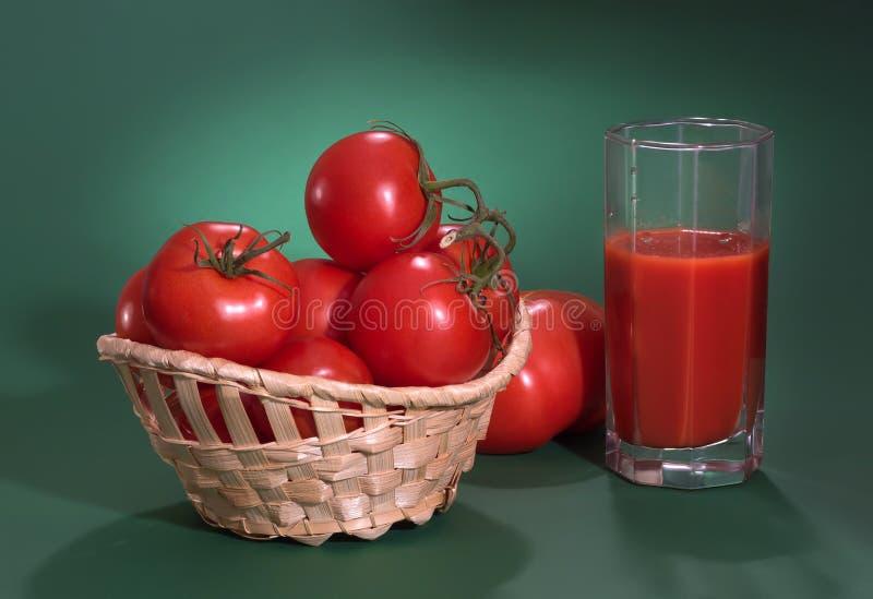 Mooie rijpe tomaten op een groene achtergrond Sap van tomaten royalty-vrije stock foto