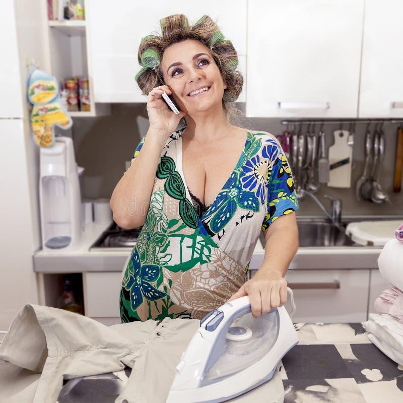 Mooie rijpe vrouw die met krulspelden kleren thuis strijken royalty-vrije stock foto