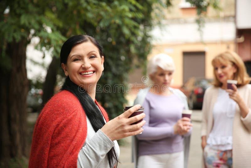 Mooie rijpe vrouw en haar vrienden die koffie in openlucht drinken stock fotografie