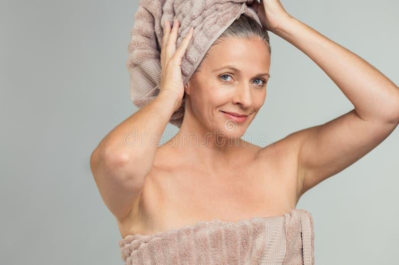 Mooie rijpe vrouw met badhanddoek stock foto