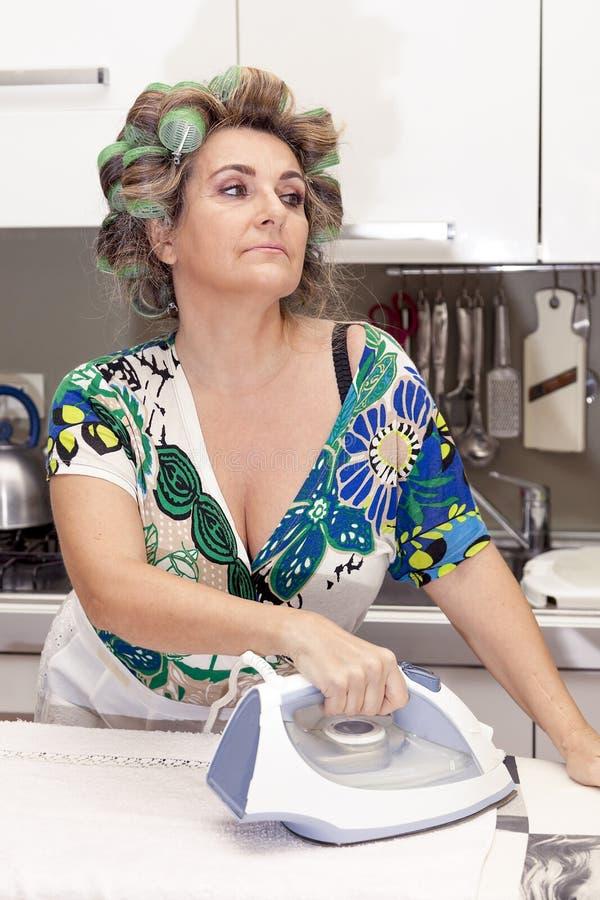 Mooie rijpe vrouw met krulspelden het strijken stock foto