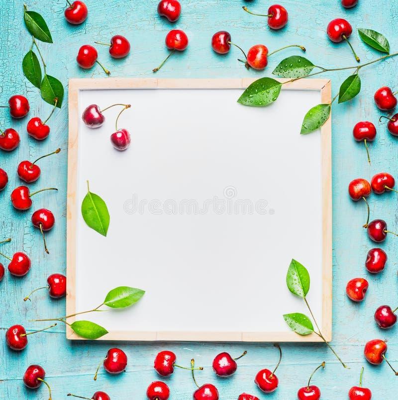 Mooie rijpe zoete kers met bladeren rond leeg wit bord, hoogste mening royalty-vrije stock afbeeldingen