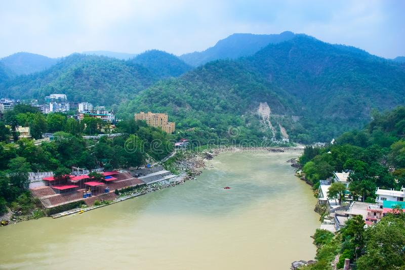 Mooie Rivier met bergen op de achtergrond en kleurrijke huizen in de kanten van de rivier Rishikesh een mooie stad in Indi stock foto