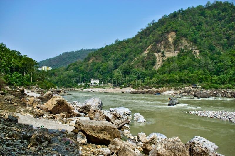 Mooie Rivier met bergen op de achtergrond en kleurrijke huizen in de kanten van de rivier Rishikesh een mooie stad in Indi stock afbeelding