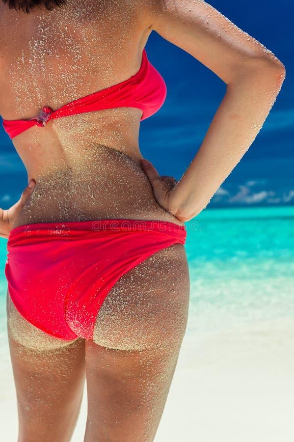 Mooie rode bikini zandige bedelaar op tropisch strand stock fotografie