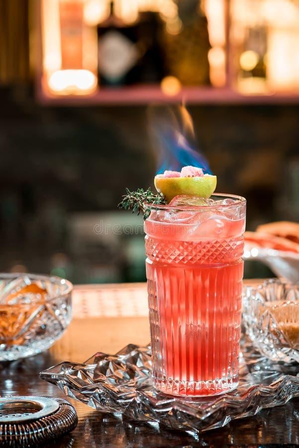 Mooie rode cocktail met ijs in gefacetteerd die glas, met het branden van kalk wordt verfraaid Cocktail op mooie kristalachtergro royalty-vrije stock fotografie