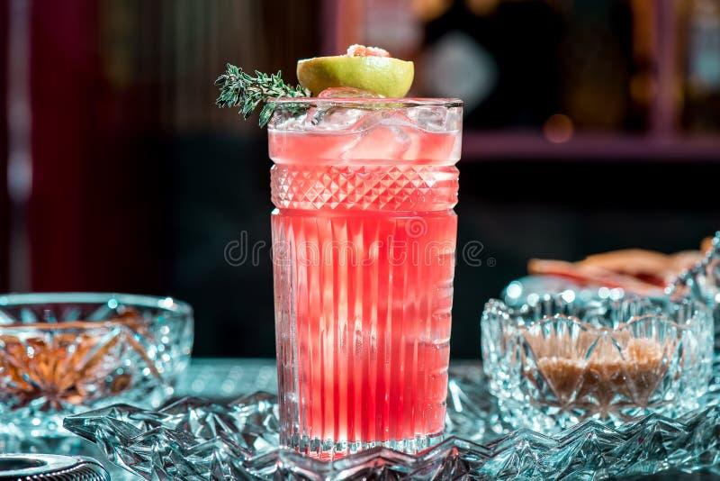 Mooie rode cocktail met ijs in gefacetteerd die glas, met het branden van kalk wordt verfraaid Cocktail op mooie kristalachtergro royalty-vrije stock foto's