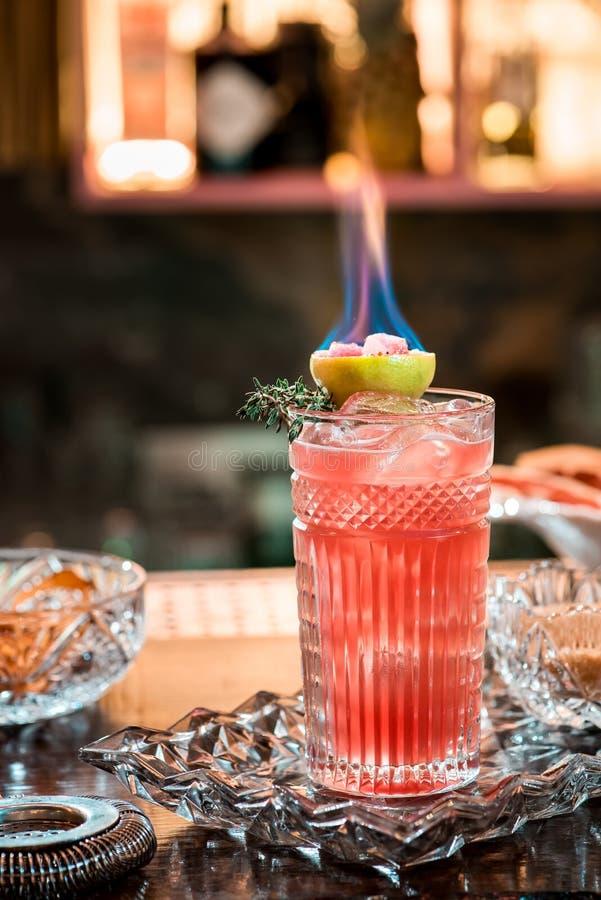 Mooie rode cocktail met ijs in gefacetteerd die glas, met het branden van kalk wordt verfraaid Cocktail op mooie kristalachtergro stock afbeeldingen