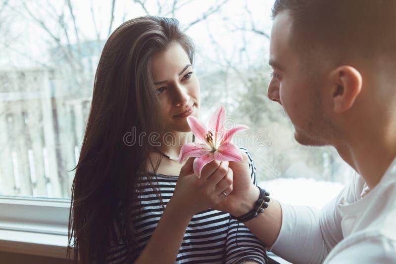 mooie romantische jonge paarman vrouw die in liefdezitting door venster elkaar bekijken die rozerode leliebloem houden royalty-vrije stock foto