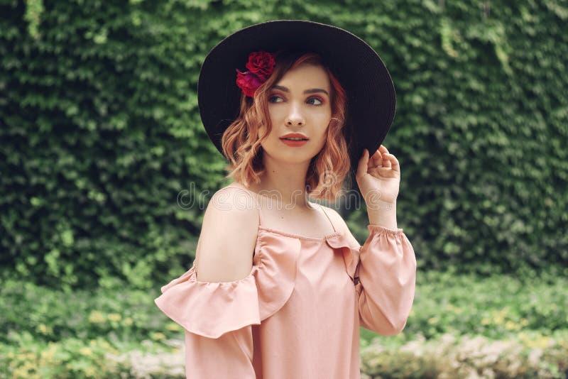 Mooie romantische jonge vrouw op een achtergrond van natuurlijke groene muur van installaties die met bloemen in hoofdhaar stelle royalty-vrije stock foto