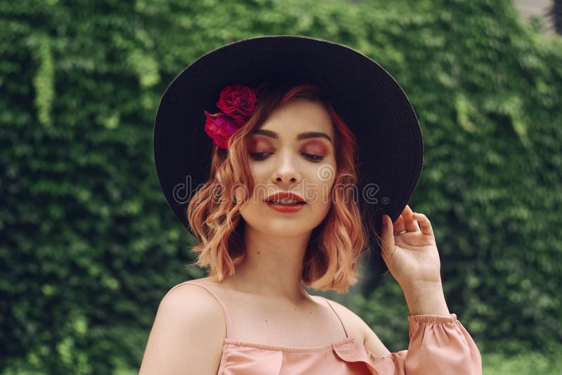 Mooie romantische jonge vrouw op een achtergrond van natuurlijke groene muur van installaties die met bloemen in hoofdhaar stelle royalty-vrije stock fotografie